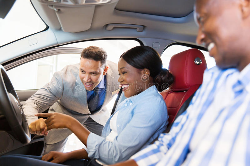 Salesman showing car couple. Salesman showing new car to african couple in showroom stock photos