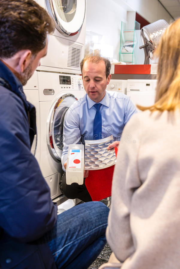 Salesman Showing Cartridge Of Washing Machine In Store royalty free stock photos