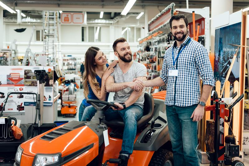 Salesman is showing couple of clients new cleaning machine in power tools store. Two men shaking hands. Salesman in checkered shirt is showing couple of clients stock image