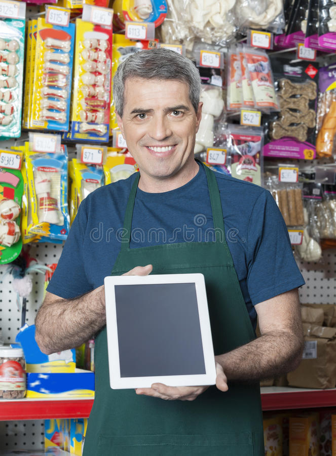 Salesman Showing Digital Tablet With Blank Screen In Pet Store. Portrait of confident salesman showing digital tablet with blank screen in pet store stock photography