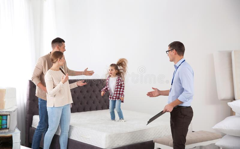 Salesman showing family mattress in store royalty free stock photos