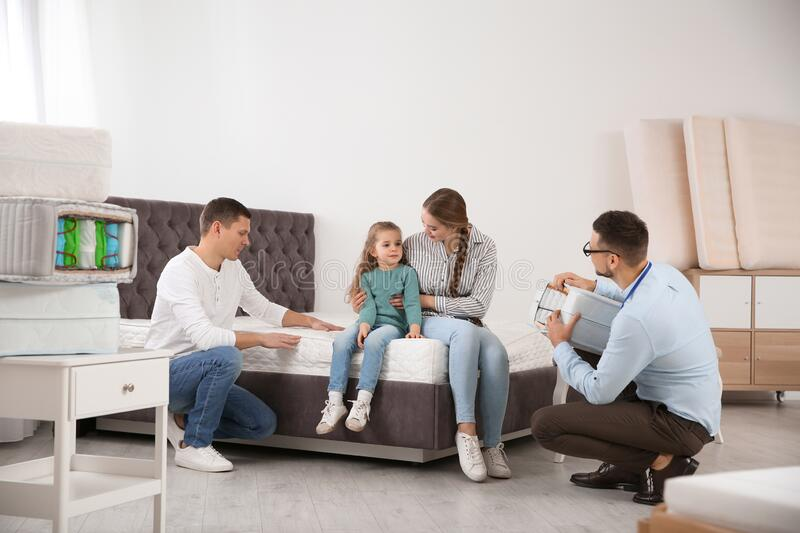 Salesman showing family section of mattress stock photos