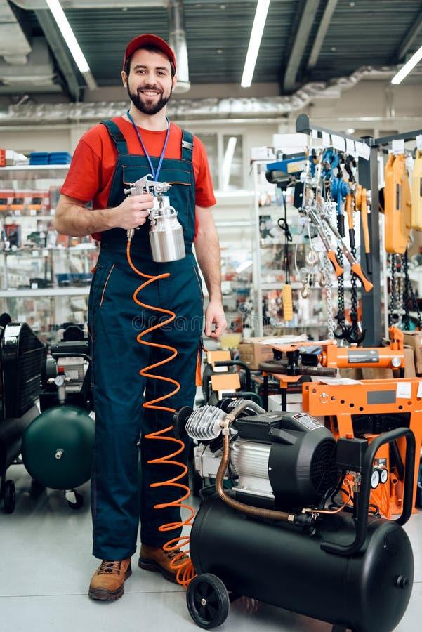 Salesman stelt zich voor met een verfspuiter van compressor op voorgrond in de werktuigmachine royalty-vrije stock foto's