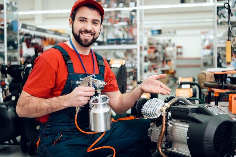 Salesman stelt zich voor met een verfspuiter van compressor op voorgrond in de werktuigmachine stock foto