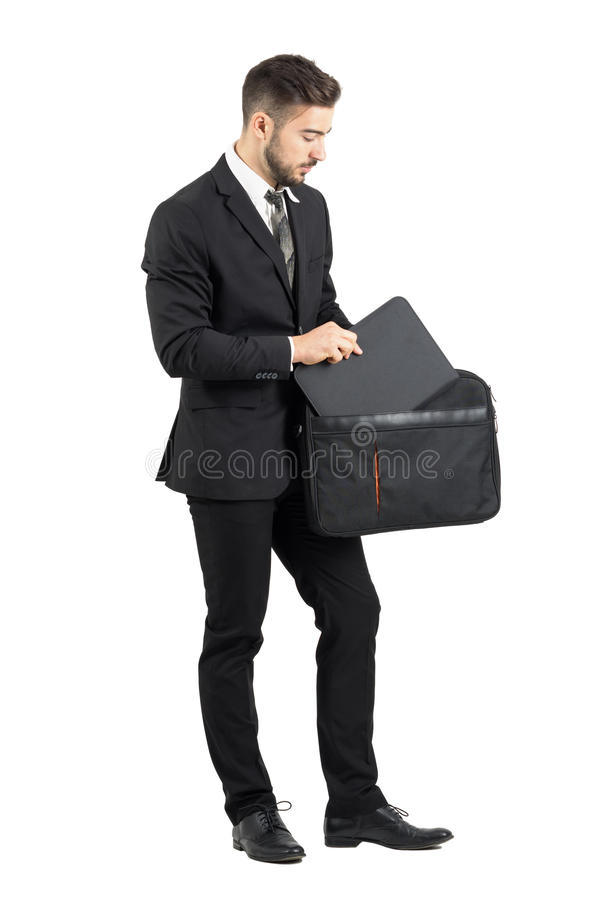 Salesman taking document folder out of briefcase. Full body length portrait isolated over white studio background royalty free stock photo