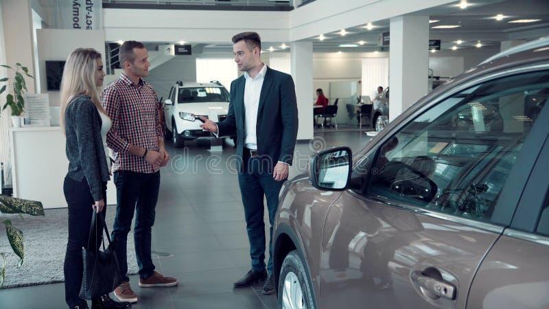 Salesman Talking to Couple inside Car Dealership stock images