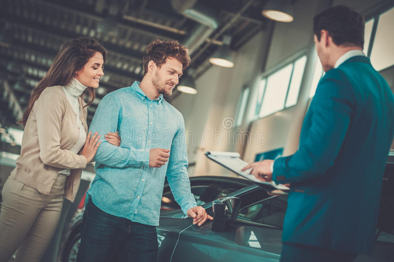 Salesman talking to a young couple at the dealership showroom. stock photos