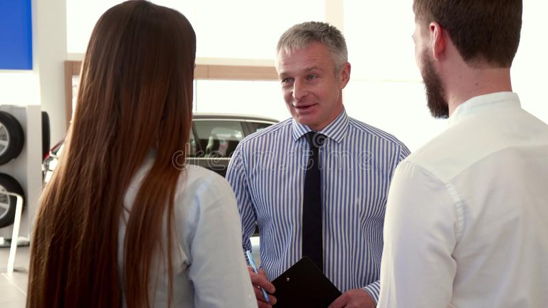 Salesman tells the couple about the car at the dealership royalty free stock images