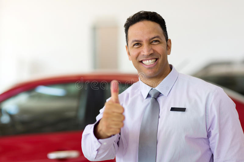 Salesman thumb up. Handsome car salesman thumb up at car dealership stock photography