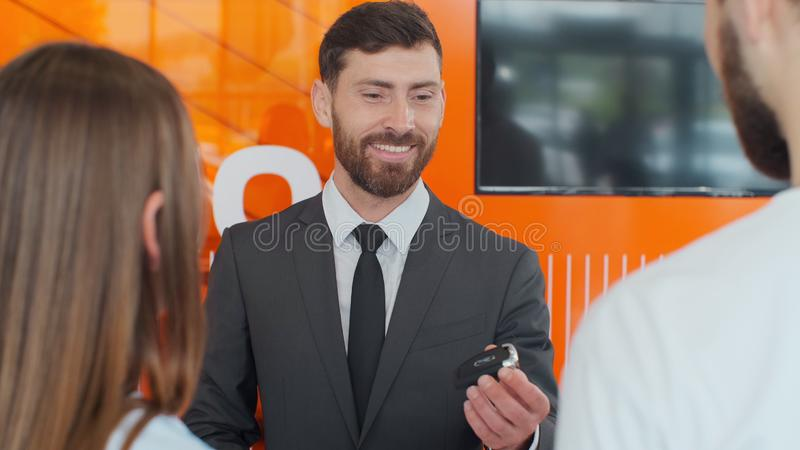 Salesman transmitting keys to young couple in car dealership. Salesman transmitting keys to young couple in car dealership stock photo