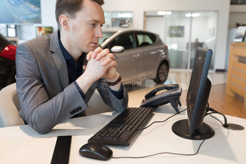 Salesman using computer while working in car showroom. Salesman with hands clasped looking at computer while working in car showroom stock photography