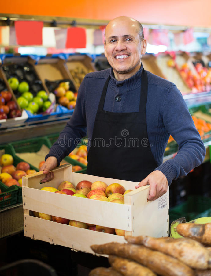 Salesman working in fruit section royalty free stock photos