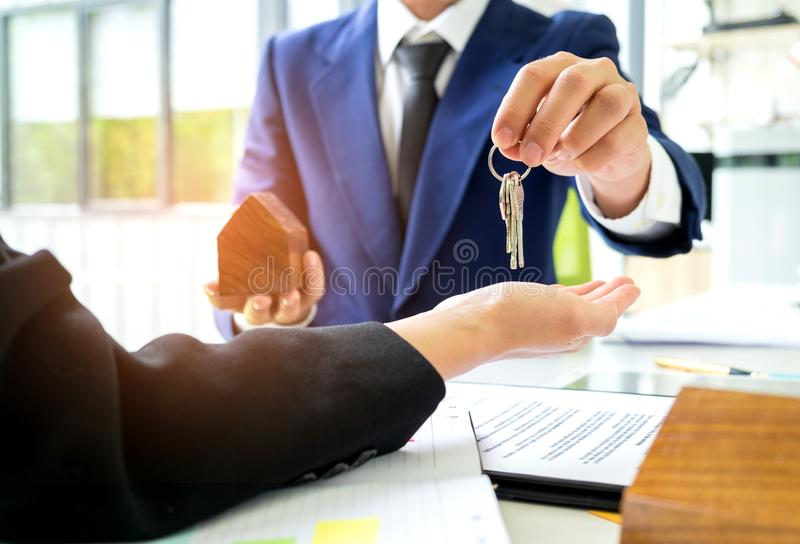 Salespeople deliver home keys to customers,Customers receive home keys from home sales sales,Home sales concept image. stock photos
