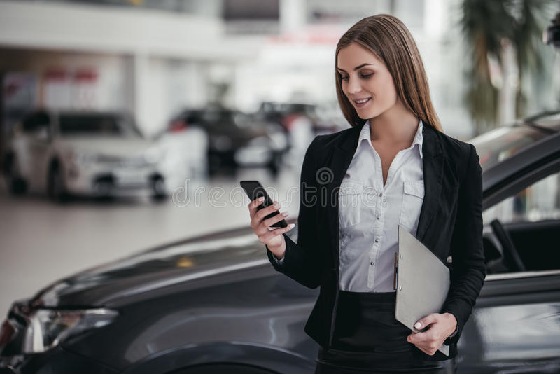 Salesperson at car dealership. Professional female salesperson at car dealership royalty free stock photos