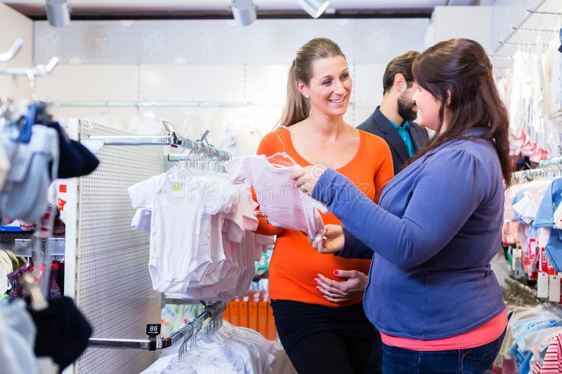 Salesperson With Couple Buying Baby Clothes In Shop Stock Image ...