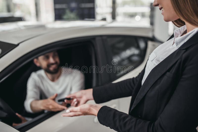Salesperson with customer in car dealership. Professional salesperson during work with customer at car dealership. Giving keys to new car owner stock image