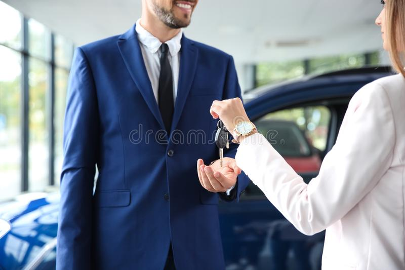 Salesperson giving car keys to man in auto dealership. Salesperson giving car keys to men in auto dealership, closeup stock photography