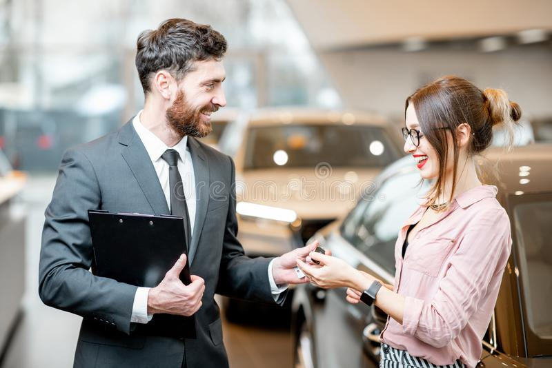 Salesperson giving car keys to a woman. Salesperson giving keys to a young happy women in the showroom with luxury cars stock photography