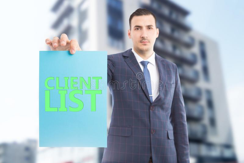 Salesperson holding paper with client list. Selective focus picture of salesperson holding blue paper with green client list text having building as background royalty free stock photography