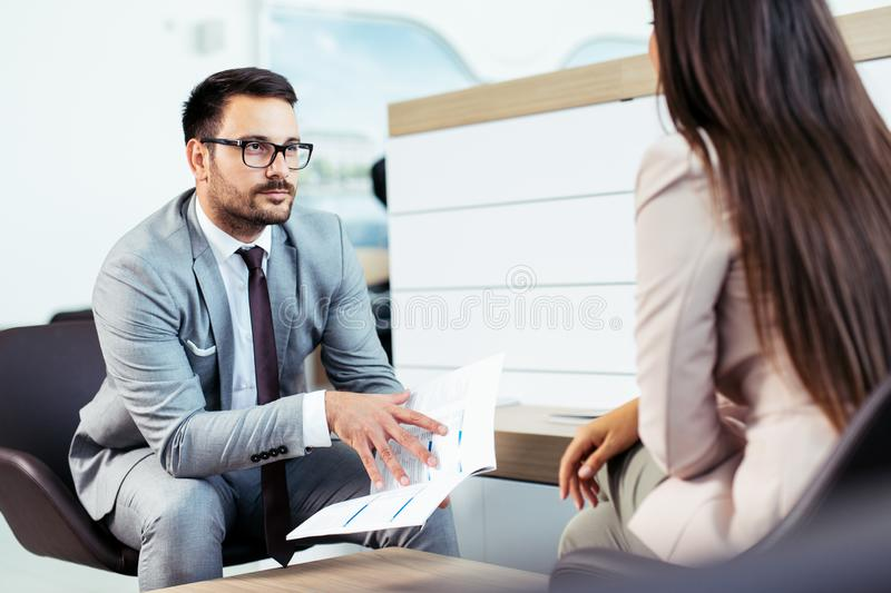 Salesperson selling cars at dealership to buyer stock image