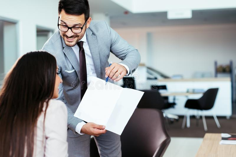 Salesperson selling cars at dealership to buyer stock photo