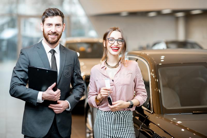 Salesperson with woman in the showroom. Portrait of a handsome salesperson with women client standing in the showroom stock photo