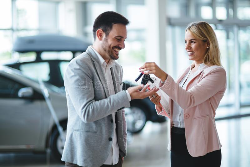Professional salesperson during work with customer at car dealership. Giving keys to new car owner. Salesperson during work with customer at car dealership royalty free stock photo