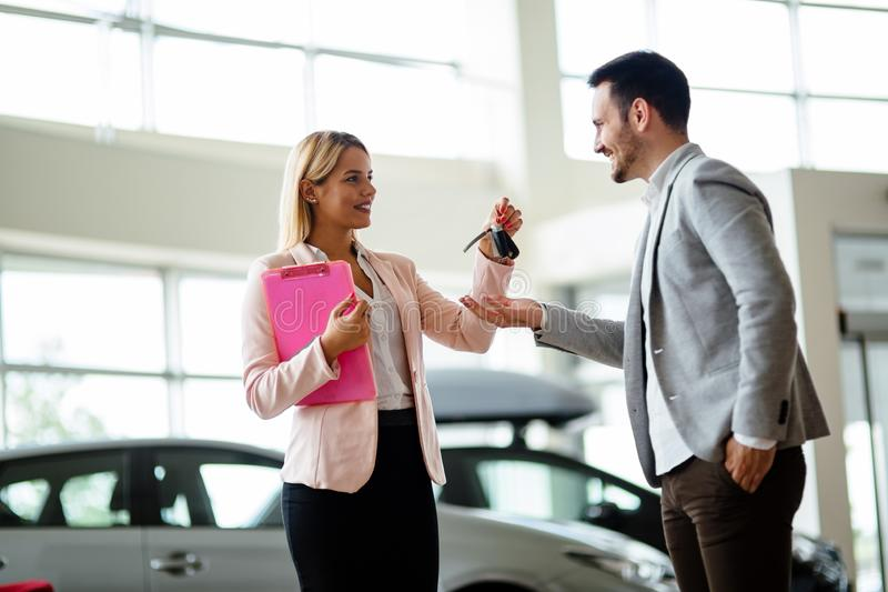 Professional salesperson during work with customer at car dealership. Giving keys to new car owner. Salesperson during work with customer at car dealership royalty free stock image