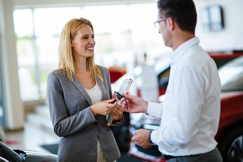 Professional salesperson during work with customer at car dealership. Giving keys to new car owner. Salesperson during work with customer at car dealership stock photos