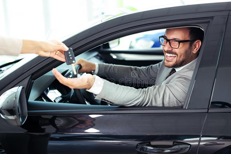 Salesperson during work with customer at car dealership. Giving keys to new car owner. Young Salesperson during work with customer at car dealership. Giving stock image