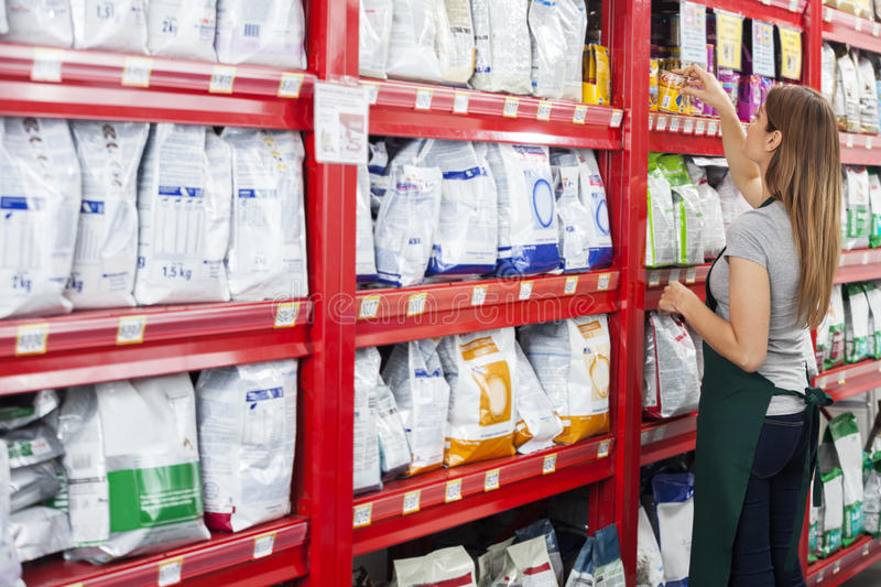 Saleswoman Arranging Food Packages In Pet Store. Side view of saleswoman arranging food packages on shelf in pet store stock image