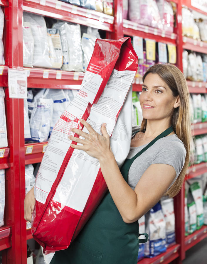 Saleswoman Carrying Food Package In Pet Store. Mid adult saleswoman carrying food package in pet store royalty free stock photos
