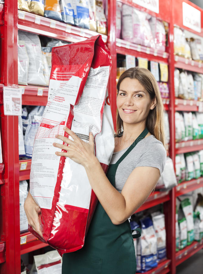 Saleswoman Carrying Large Food Package In Pet Store. Portrait of confident saleswoman carrying large food package in pet store royalty free stock images
