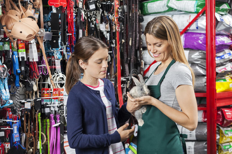 Saleswoman Holding Rabbit With Girl At Pet Store. Smiling saleswoman holding rabbit while standing with girl at pet store stock photography