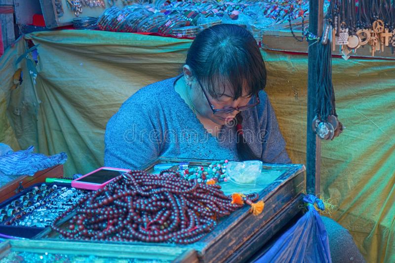 Saleswoman of jewelry and amulets. India, Dharamsala - March 11, 2018: saleswoman of cheap jewelry and amulets stock photography