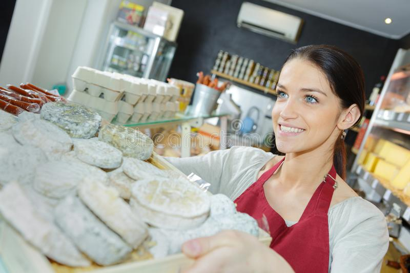 Saleswoman selling cheese to man in grocery store stock photo