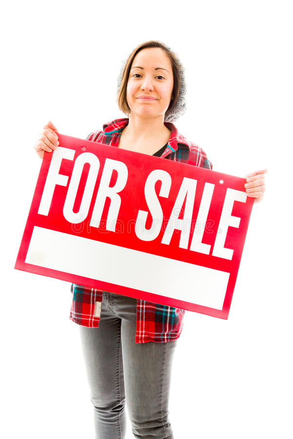 Saleswoman showing a for sale sign. Caucasian young adult woman in studio isolated on white background royalty free stock photos