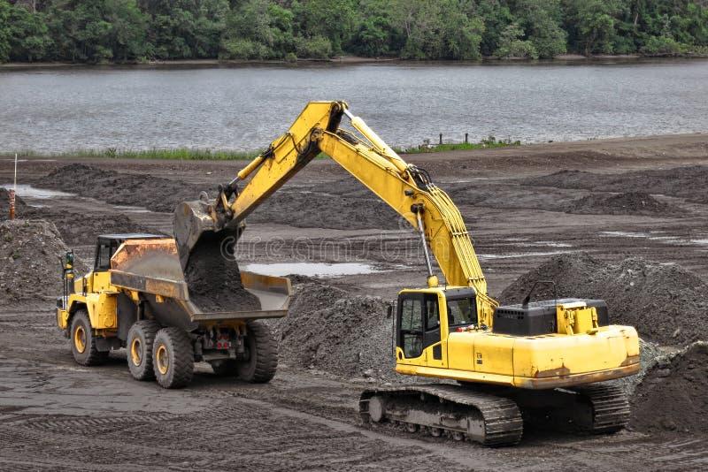 Saleté de charge d'excavatrice de construction dans le camion photo libre de droits