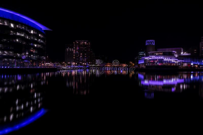 Salford Quays, England, UK, October 9, 2018 A Night time landscape using long exposure of Media City UK showing reflections on th. E Manchester Ship Canal at stock photography