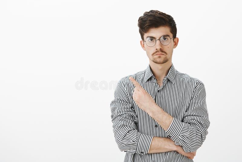 Salga, no quiera le ven Cansado compañero de trabajo masculino europeo enojado en vidrios y camisa rayada, señalando detrás o en fotos de archivo libres de regalías
