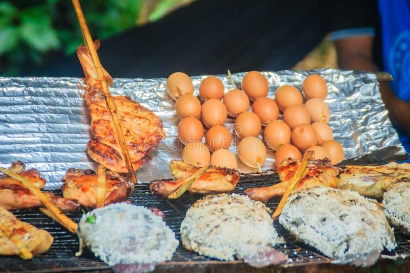 Salgue os peixes revestidos do tilapia que grelharam no fogão do carvão vegetal Galinha grelhada na vara de bambu e em ovos grelh imagem de stock royalty free