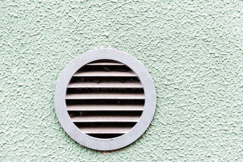 Salida de aire plástica circular en la parrilla verde blanca de la ventilación de la pared imagen de archivo