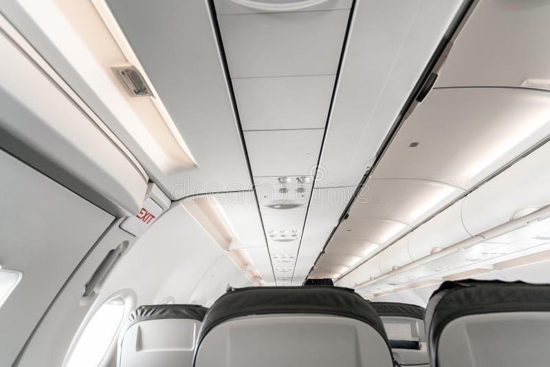 Salida de emergencia en un avión, vista desde adentro del avión Asientos vacíos del aeroplano en la cabina Transporte moderno imagen de archivo libre de regalías