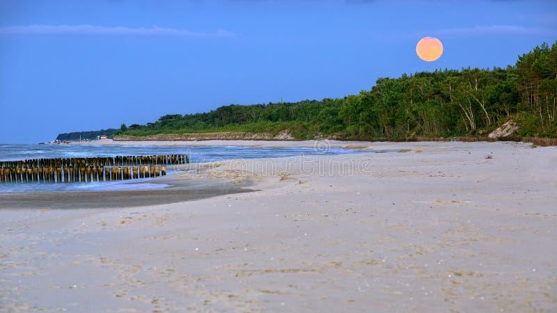 Salida de la luna en la playa en el mar Báltico imagenes de archivo