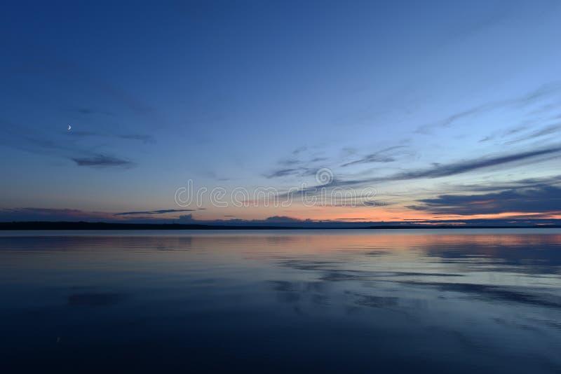 Salida de la luna en la luz crepuscular en el cielo azul en la puesta del sol sobre el agua reservada del espejo del lago imágenes de archivo libres de regalías