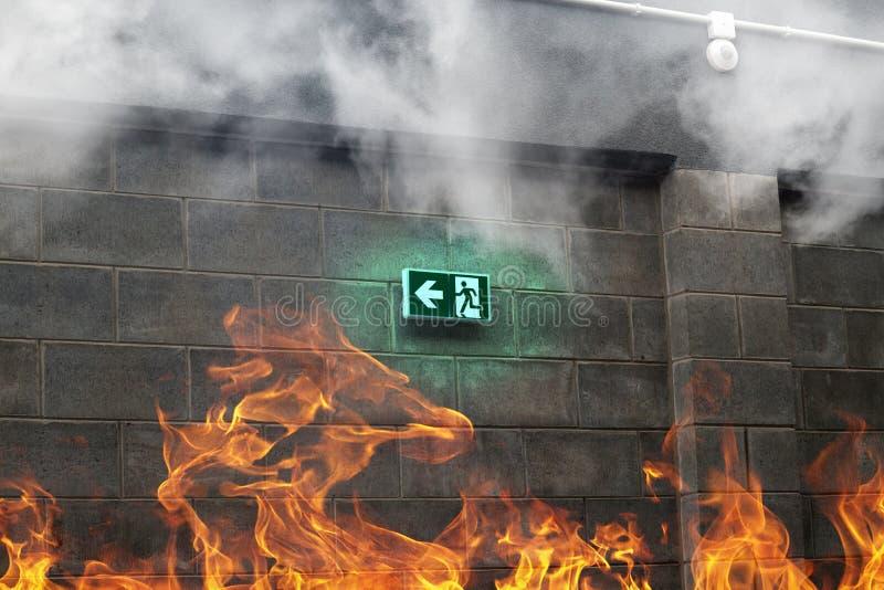 Salida de socorro de la emergencia en la pared de piedra con el fuego y el humo foto de archivo