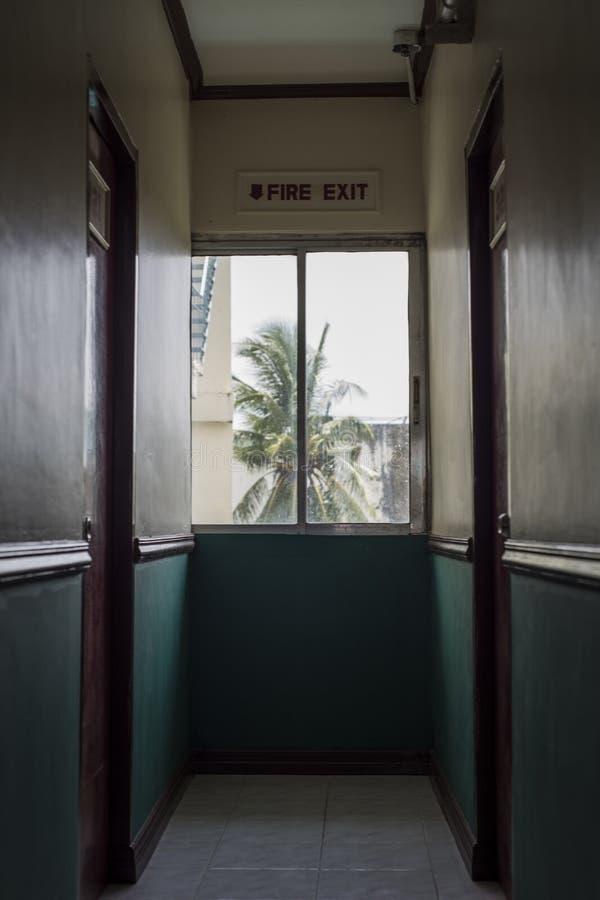 Salida de socorro en un pasillo del hotel con un árbol de coco fuera de la ventana imágenes de archivo libres de regalías