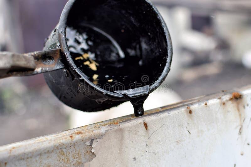 Salida del alquitrán negro caliente derretido de la taza del metal en superficie con vapor imagen de archivo