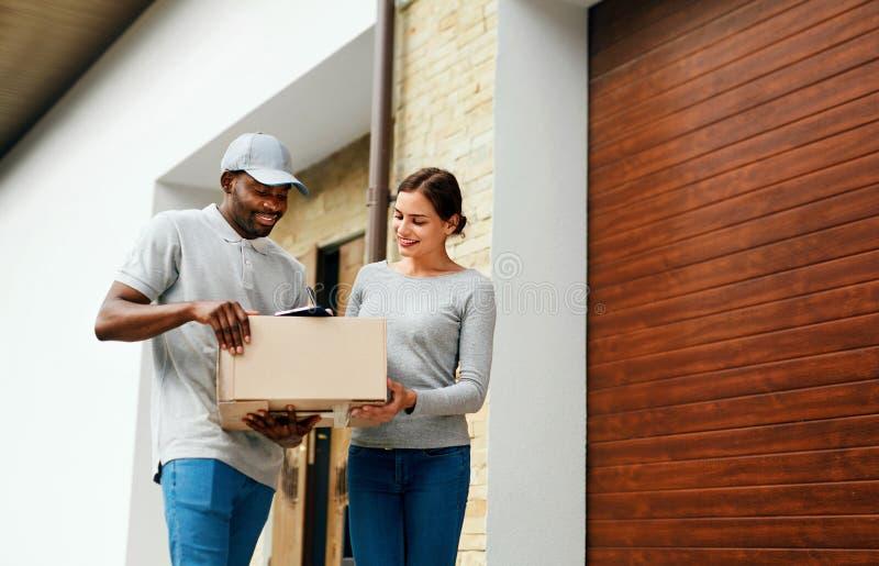 Salida del conjunto Mujer de Delivering Box To del mensajero del hombre en casa imagenes de archivo