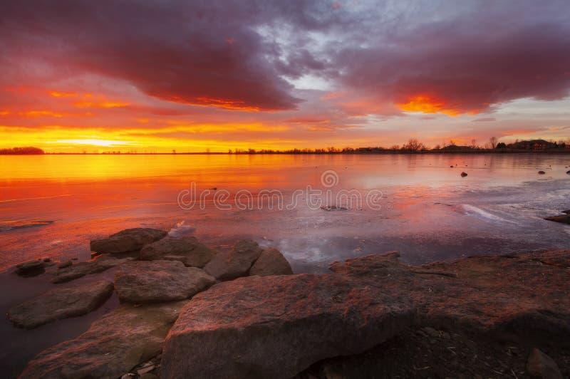 Salida del sol ardiente sobre un lago congelado winter con las rocas en el primero plano fotografía de archivo libre de regalías
